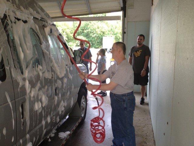 Individuals and staff washing the PEACE Van before detailing it.